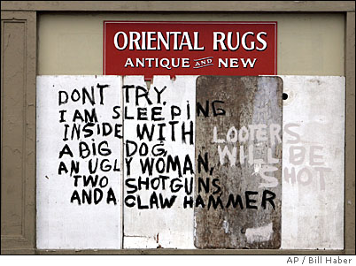 A hand-painted sign outside a New Orleans business warns away looters in the wake of Hurricane Katrina Thursday, Sept. 1, 2005. Ethicists and social psychologists said in interviews that rules of human behavior _ including respect for others' property and for social order itself _ dissolve quickly in desperate circumstances like the storm's aftermath. (AP Photo/Bill Haber)